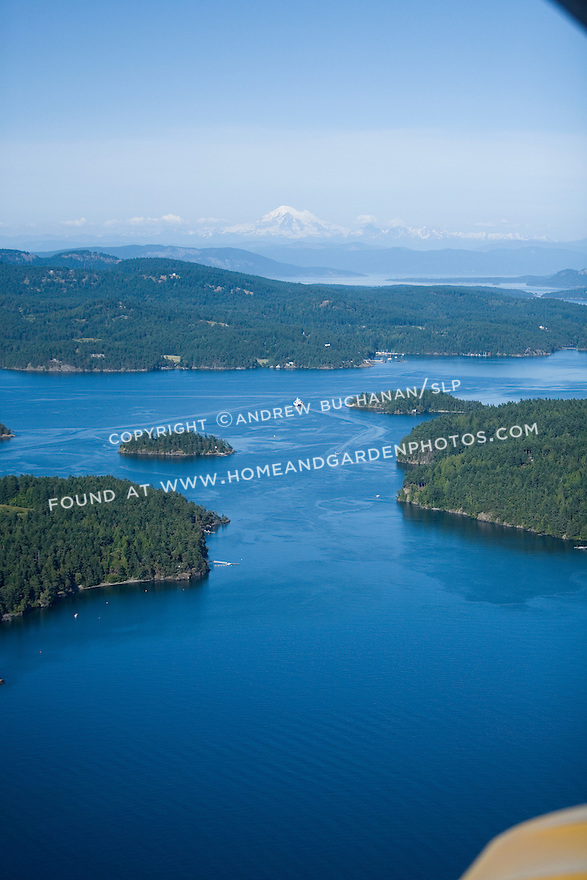 A white Washington State car ferry makes its way toward Orcas Island, in the deep blue summer waters of the San Juan islands as seen from the air.  Snow-capped Mt. Baker rises in the distance.