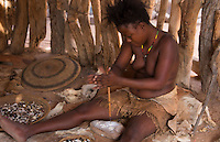 Namibia Africa Damara tribe traditional life in Damaraland in Damara Living Museum crushing ostrick egg shell jewelry, handmade art crafts