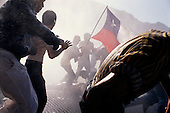 Santiago, Chile<br /> October 1988<br /> <br /> Prior to the plebiscite vote a Chilean flag waves in defiance amid a shroud of police tear gas and direct fire of a water canon.<br /> <br /> In October 1988, General Augusto Pinochet ordered a plebiscite vote asking Chilean citizens whether he should continue in office. It produced a decisive &quot;no&quot; vote and the following year he lost the first presidential election in 19 years. However, under a constitution crafted by his advisors, he remained as army commander until 1998. <br /> <br /> Pinochet continued to wield enormous power until his arrest in London on human rights charges in October 1998.