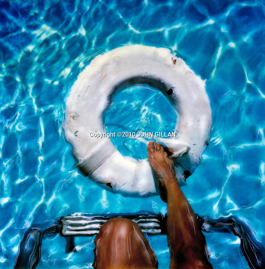 Woman's leg reaching for white inner tube in blue pool from ladder. Artistic  image created with the  SX70 Polaroid etching technique