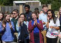 NWA Democrat-Gazette/ANDY SHUPE<br /> Ceci Allen, 12; (from left) Rachel Leach, 13; Dezi Tartaglia, 13; and Amena Soliman, 13; all eighth-graders at Haas Hall Academy, applaud Tuesday, Sept. 22, 2015, as the ribbon is cut to officially open the school's Starr Scholar Center in Fayetteville. The newly renovated facility is located at 380 N. Front Street and is named in honor of Billie Jo Starr and her family.