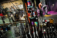 A bicycle painter and a bicycle mechanic are seen working in a small scale bicycle factory in Bogota, Colombia, 10 April 2013. Due to the strong, vibrant cycling culture in Colombia, with cycling being one of the two most popular sports in the country, dozens of bike workshops and artisanal, often family-run bicycle factories were always spread out through the Colombian cities. However, growing import of cheap bicycles and components from China during the last decade has led to a significant decline in domestic bicycle production. Traditional no-name bike manufacturers are forced to close down their factories, struggling to survive in the competitive bicycle market.