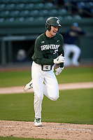 Catcher Scott Combs (35) of the Michigan State Spartans runs out a batted ball in a game against the Merrimack Warriors on Saturday, February 22, 2020, at Fluor Field at the West End in Greenville, South Carolina. Merrimack won, 7-5. (Tom Priddy/Four Seam Images)