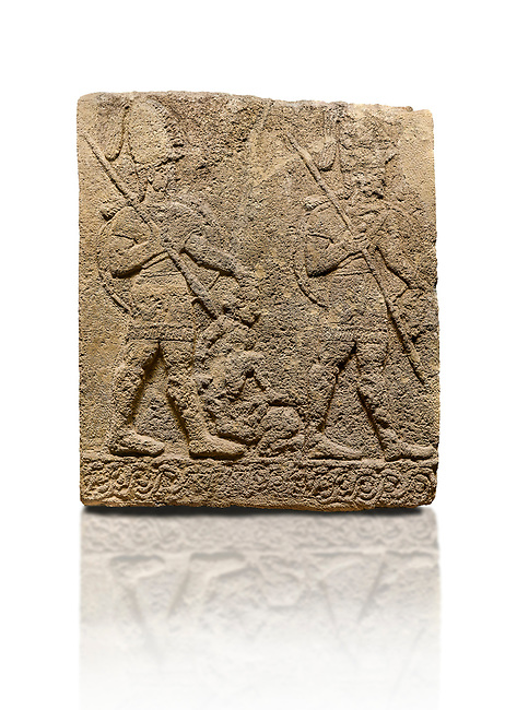 Hittite sculpted Orthostats panel of Long Wall Limestone, Karkamıs, (Kargamıs), Carchemish (Karkemish), 900-700 B.C. Soldiers. Anatolian Civilisations Museum, Ankara, Turkey<br /> <br /> Figure of two helmeted warriors. They have their shield in their back and their spear in their hand. The prisoner in their front is depicted small. A human head is depicted in the left hand of the warrior in the front. The warrior at the rear holds the prisoners sitting on his lap from his hair. Below this figure, which was described small, lies yet another small human figure. <br /> <br /> On a White Background.