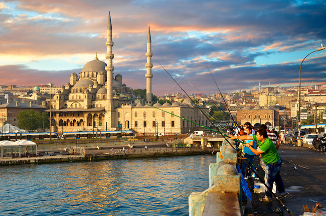 Fisherman on the Galata bridge fishing in the Golden Horn next to The Yeni Camii, The New Mosque or Mosque of the Valide Sultan ordered by Safiye Sultan in 1597, Istanbul Turkey.