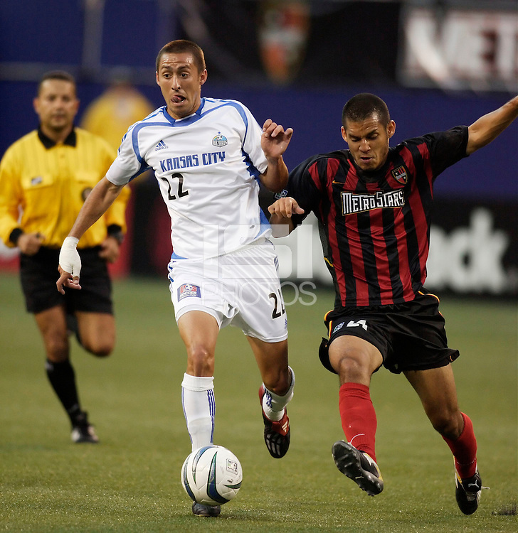 The Wizard's Davy Arnaud battles for the ball with the MetroStars' Craig Ziadie as referee Hector Tobon trails. The Kansas City Wizards were defeated by  the NY/NJ MetroStars to a 1 to 0 at Giant's Stadium, East Rutherford, NJ, on May 30, 2004.