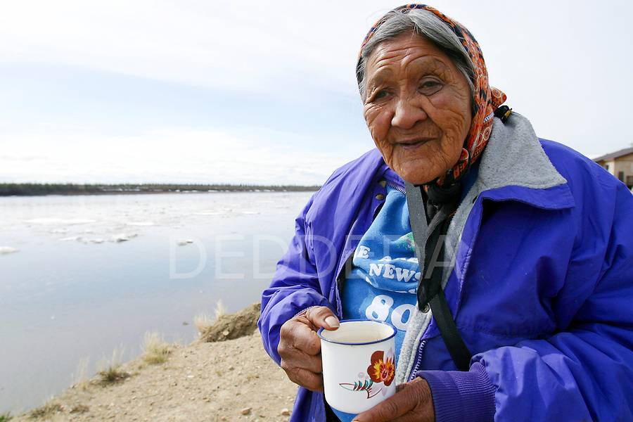 Elder Edith Josie, an elder in the Vuntut Gwitchin First Nation, enjoys her cup of tea as she stands next to the Porcupine River, in Old Crow, Yukon Territory, Canada..