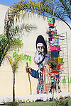Public art in the making:<br /> <br /> Street muralist atop scaffold creates a work of art on side of a tall building.