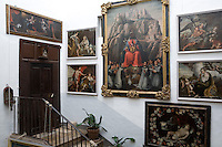 A gallery of religious and allegorical paintings welcomes visitors to the first floor entrance door of antiqarian Enric Serraplanas' Spanish residence