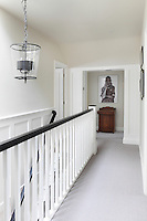 A staircase landing with white panelling on the stairwell walls