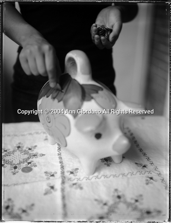 Young girl placing money in piggy bank