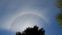 Partial sun halo created by clouds at sunrise.