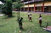 JAIPALGURI, INDIA- AUGUST 16: Player and coach of the female football team, the Dooars XI,  Bhabani Munda, 24, sweeps up the yard at the local school  where she works part-time during the day on August 16, 2013 at the Kalchini tea estate In Jalpaiguri district , West Bengal, India. The Kalchini tea estate where Bhabani Munda lives is one of the most interior and backwards regions in north Bengal. The tea estates of North Bengal, including the Kalchini tea estate, were in news in 2007-08 for large-scale starvation deaths owing to malnutrition. Even today one person dies every day due to starvation in the north Bengal tea estates. In the last decade there have been 3500 deaths in these tea estates. (Photo by Daniel Berehulak for Time Magazine)