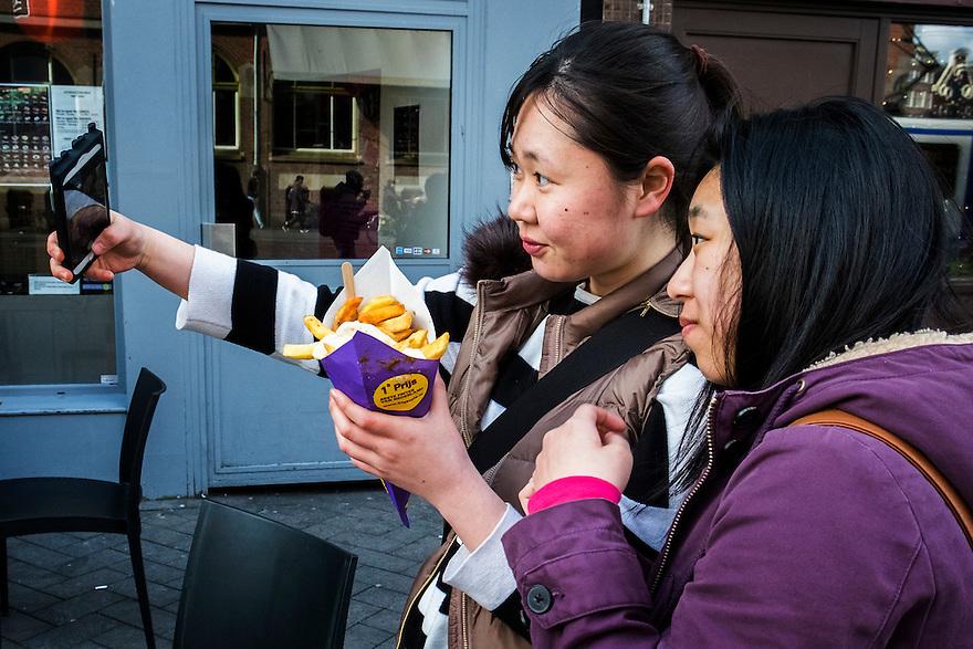 Nederland, Amsterdam, 30 maart 2016<br /> Chinese, asiatische toeristen maken een selfie met de grote zak patat die ze net hebben gekocht.<br /> Er zijn veel chinezen in de stad, momenteel.<br /> <br /> Foto (c) Michiel Wijnbergh