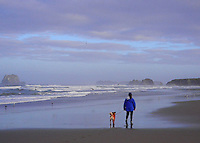 Girl with her dog stroll Bandon Beach during low tide as the sun rises. Bandon, Oregon. (Digitally edited for a painterly appearance).