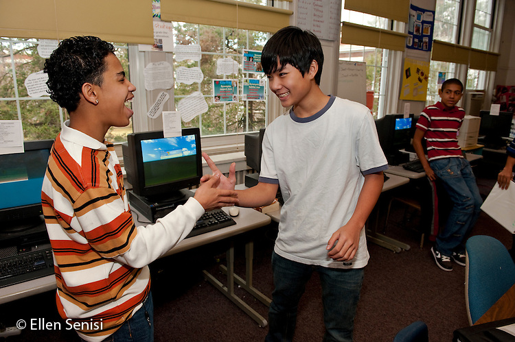 MR / Schenectady, NY. Mont Pleasant Middle School (urban public school). English as a Second Language classroom (ESL). Students greet each other with unique handshake as they arrive for class. Boy at left; 14; grade 8; Puerto Rican-American; recent immigrant. Boy at right; 13; grade 8; Vietnamese-American; recent immigrant. MR: San9, Tra2. ID: AJ-esl1. © Ellen B. Senisi