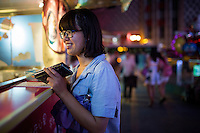 "Ge Xin Wei gets a snack from a food stall in Deyi World Plaza near the Jiafengbei central business district in Yuzhong district, Chongqing, China. Ge Xin Wei is part of a group of college students from Hubei Province who had spent their summer vacation as volunteer teachers in Guizhou Province and stopped in Chongqing on the way back to their hometowns. Ge Xin Wei (in blue) said that they came to Deyi World because they'd heard the area was a popular place to go at night. ""The food is delicious and spicy,"" she said."