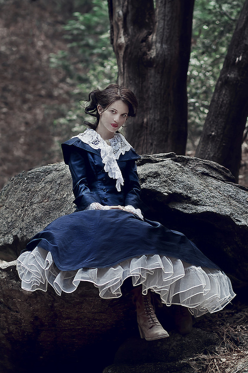 Young woman wearing long blue silk dress sitting alone in woods