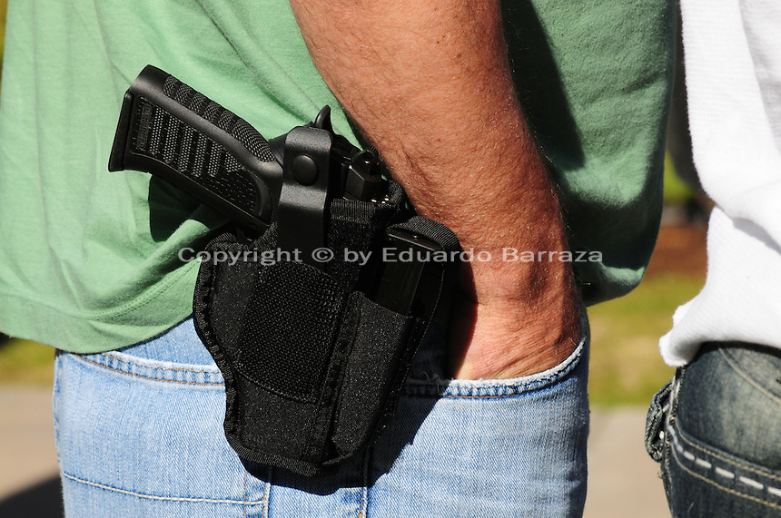 """Phoenix, Arizona. January 19, 2013 - A demonstrator displays a gun on his waist during Saturday's rally in Phoenix to oppose potential legislation to limit access to guns and ammunition. As President Barack Obama proposed new gun regulations last week, gun owners demonstrated against it with national """"Guns Across America"""" rallies to defend the Second Amendment. Dozens showed up at the Arizona State Capitol, many of them carrying weapons. Photo by Eduardo Barraza © 2013"""