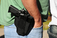 "Phoenix, Arizona. January 19, 2013 - A demonstrator displays a gun on his waist during Saturday's rally in Phoenix to oppose potential legislation to limit access to guns and ammunition. As President Barack Obama proposed new gun regulations last week, gun owners demonstrated against it with national ""Guns Across America"" rallies to defend the Second Amendment. Dozens showed up at the Arizona State Capitol, many of them carrying weapons. Photo by Eduardo Barraza © 2013"