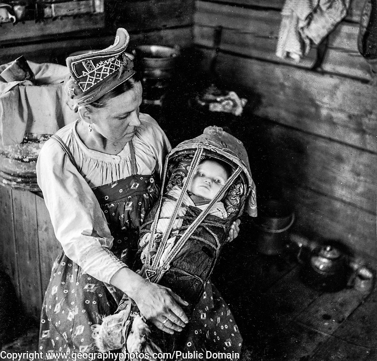 """Winter village. Skolt Sami woman and her child. The mother is wearing a pearl embroidered """"shamtshik""""."""