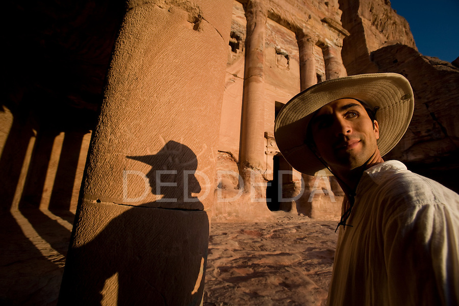 A male tourist in a hat stands near the entrance to the Um Tomb in the Nabatean ancient city of Petra, Jordan.