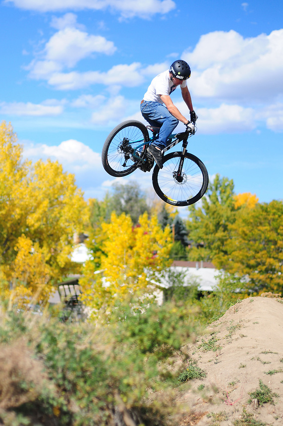 "A mountain biker bmx dirt jumping at the ""Sunset trails"" in Lakewood, Colorado on October 19, 2008. alternative sports; extreme; danger; foliage; clouds; air; dirt; sunset trails"