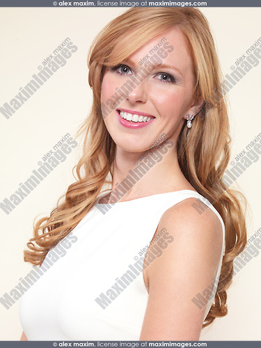 Portrait of a beautiful young woman with long blond hair isolated on light beige background
