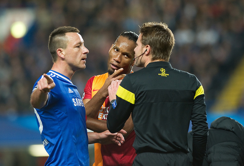 Chelsea's John Terry and Galatasaray's Didier Drogba question Referee Felix Brych <br /> <br /> Photo by Ashley Western/CameraSport<br /> <br /> Football - UEFA Champions League First Knockout Round 2nd Leg - Chelsea v Galatasaray - Tuesday 18th March 2014 - Stamford Bridge - London<br />  <br /> &copy; CameraSport - 43 Linden Ave. Countesthorpe. Leicester. England. LE8 5PG - Tel: +44 (0) 116 277 4147 - admin@camerasport.com - www.camerasport.com
