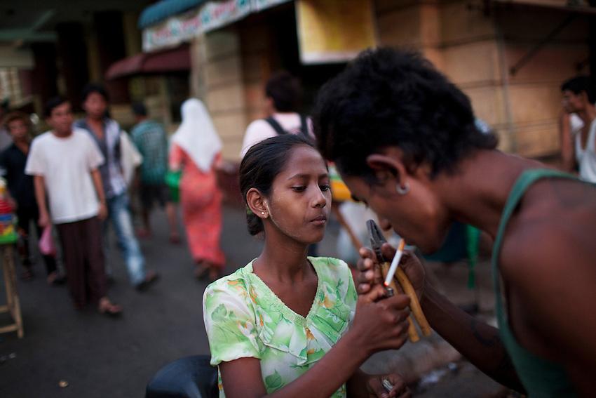 A woman lights a cigarette for a rickshaw driver in downtown Yangon, Myanmar, March 26, 2012.