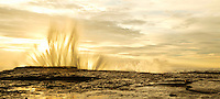 water sprays into the sky as waves are crashing and splashing at sunset