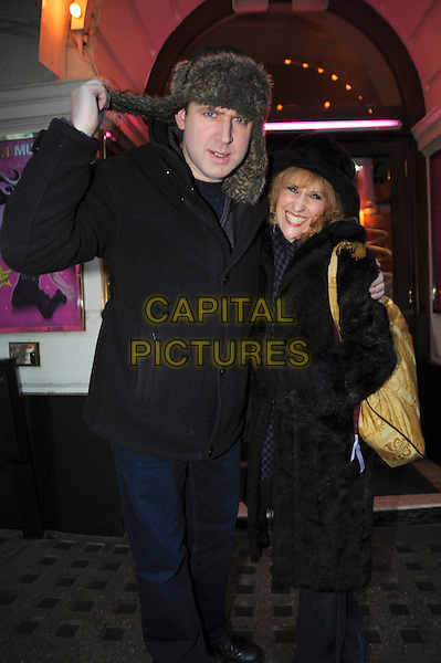 """TIM VINE & ANITA DOBSON .Leaving after a performance of """"Grease"""" the musical, Piccadilly Theatre, London, England, UK, 26th November 2010..half 3/4  length hat black coat fur bag gloves arm around jeans jacket deer stalker .CAP/IA.©Ian Allis/Capital Pictures."""