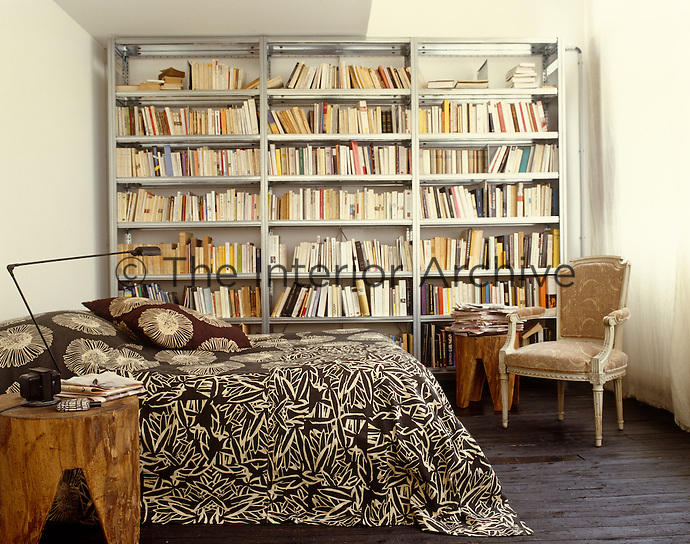 One wall of the bedroom is taken up with industrial  book shelves and the bed is draped in one of Dominique Picquier's fabrics