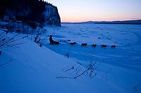 Cim Smyth drops down the bank onto the Yukon River shortly after leaving the Ruby checkpoint at sunset during the 2010 Iditarod Sled Dog Race, Alaska