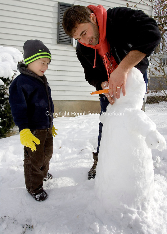 WATERBURY CT. 15 December 2013-121513SV02-Noel Velo, 5, of Waterbury makes sure his dad, Ferdinano Velo, gets the snowman&rsquo;s nose on straight on Highland Avenue in Waterbury Sunday.<br /> Steven Valenti Republican-American