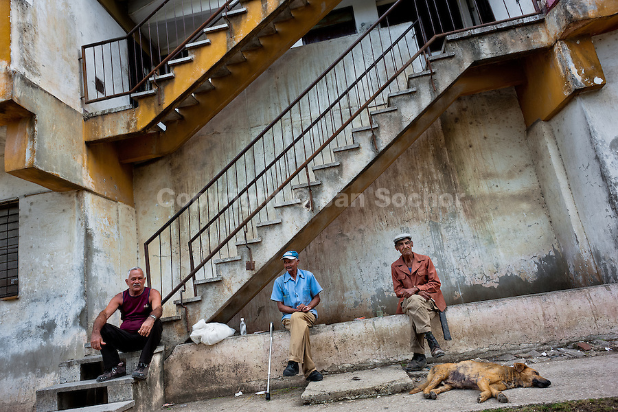 """Old Cuban men sit and drink rum in front of the apartment block in Bahía, a public housing periphery of Havana, Cuba, 11 February 2011. The Cuban economic transformation (after the revolution in 1959) has changed the housing status in Cuba from a consumer commodity into a social right. In 1970s, to overcome the serious housing shortage, the Cuban state took over the Soviet Union concept of social housing. Using prefabricated panel factories, donated to Cuba by Soviets, huge public housing complexes have risen in the outskirts of Cuban towns. Although these mass housing settlements provided habitation to many families, they often lack infrastructure, culture, shops, services and well-maintained public spaces. Many local residents have no feeling of belonging and inspite of living on a tropical island, they claim to be """"living in Siberia""""."""