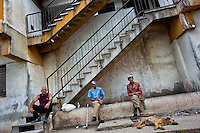 "Old Cuban men sit and drink rum in front of the apartment block in Bahía, a public housing periphery of Havana, Cuba, 11 February 2011. The Cuban economic transformation (after the revolution in 1959) has changed the housing status in Cuba from a consumer commodity into a social right. In 1970s, to overcome the serious housing shortage, the Cuban state took over the Soviet Union concept of social housing. Using prefabricated panel factories, donated to Cuba by Soviets, huge public housing complexes have risen in the outskirts of Cuban towns. Although these mass housing settlements provided habitation to many families, they often lack infrastructure, culture, shops, services and well-maintained public spaces. Many local residents have no feeling of belonging and inspite of living on a tropical island, they claim to be ""living in Siberia""."