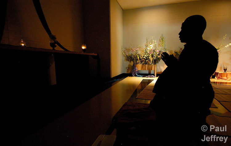 At the XV International AIDS Conference in Bangkok in 2004, a Buddhist monk meditates in the Interfaith Prayer Room. Faith-based organizations were much more prominent in the conference than in past events.