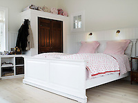 One of the bedrooms at Heegaard house is clad in white tongue and groove panelling with cheerful soft furnishings in pink