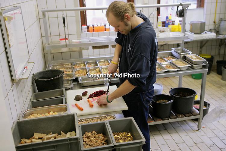 Foto: VidiPhoto..ARNHEM - Dierenverzorger Christiaan Luttenberg aan het werk in Burgers' Zoo. Foto: Voedsel klaar maken in de centrale keuken..