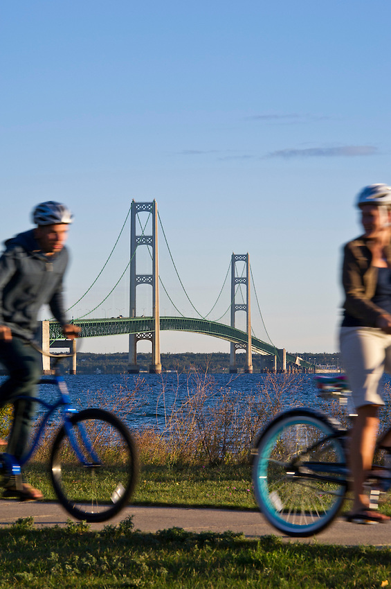 A couple rides bikes at a park with a view of the Mackinac Bridge in Mackinaw City, Michigan.