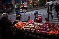 A woman sells fruits in a street at Manhattan's Chinatown in New York, Nov 11, 2013. VIEWpress/Eduardo Munoz Alvarez