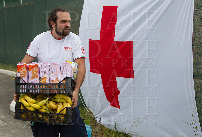Un operatore della Croce Rossa porta del cibo nella tendopoli allestita presso la stazione Tiburtina a Roma, 16 giugno 2015.<br /> A health worker carries food into the tent camp set up near the Tiburtina railway station in Rome, 16 June 2015. Italy is facing a huge flow of migrants brought to Sicily after rescue at sea, many of whom are trying to join their relatives in northern Europe. <br /> UPDATE IMAGES PRESS/Riccardo De Luca