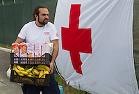 Un operatore della Croce Rossa porta del cibo nella tendopoli allestita presso la stazione Tiburtina a Roma, 16 giugno 2015.<br />
