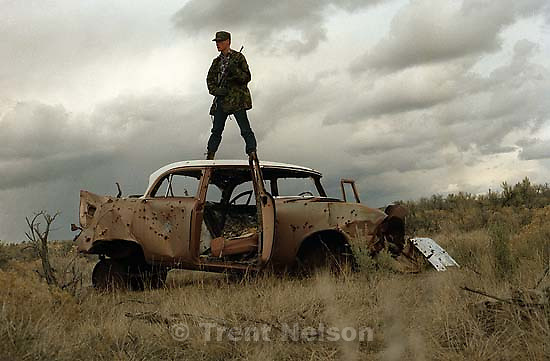 Trent Nelson in camo with gun on old car.<br />