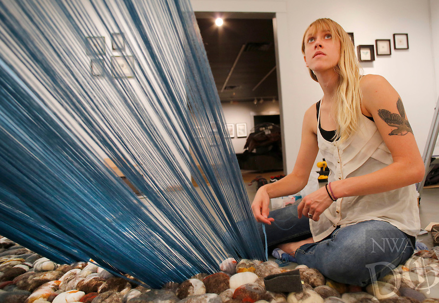 "NWA Democrat-Gazette/DAVID GOTTSCHALK  Amber Imrie-Situnayake, of Oakland, Cal., works on her interactive fiber installation ""Buffalo"" in the Fayetteville Undergound Wednesday, August 5, 2015. The piece duplicates the topography of the Buffalo river and is made of 1,000 hand felted wool stones and more than 200,000 (cq) yards of thread. The art studio will be open and participating in First Thursday Fayetteville activities tonight on the square."