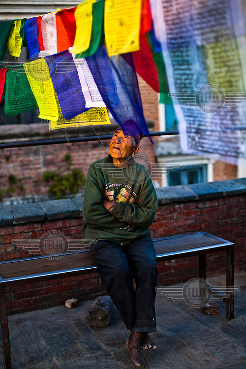 An elderly man looks up at prayer flags flying at Syambhunath Gompa.