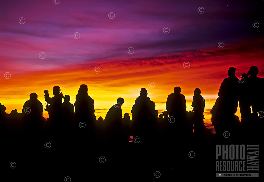 People enjoy the predawn light show preceding sunrise at 9,740 feet on Mt. Haleakala in Haleakala National Park, Maui.