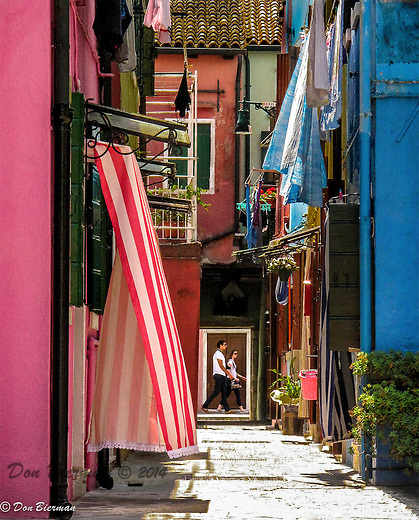 Tourest rush by a colorful allyway on their way to the markets, Burano, a small island off Venice, Italy.