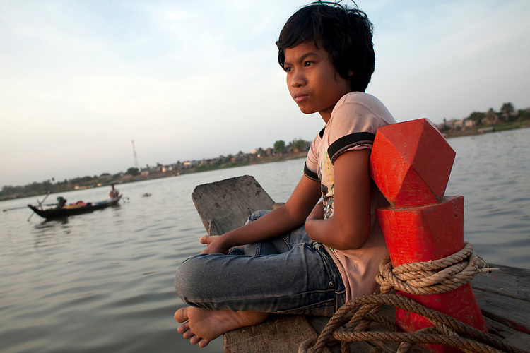 A young boy watches fisherman at work on the Mekong River early in the morning outside of Phnom Penh, Cambodia. <br /> <br /> Photos &copy; Dennis Drenner 2013.